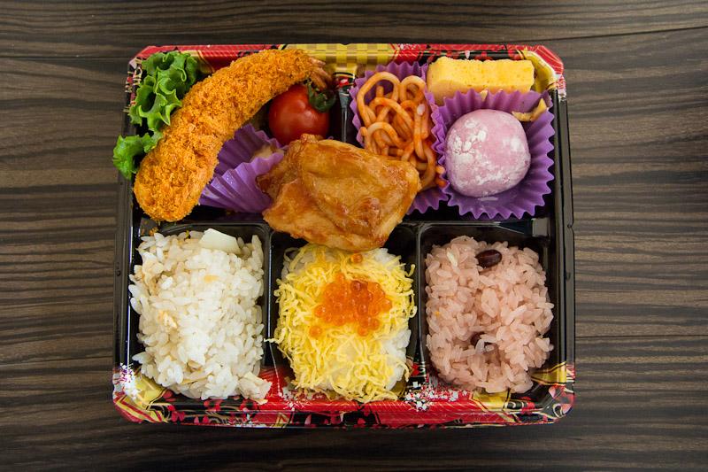 Bentō du supermarché avec poulet, tempura de crevette, spaghetti, omelette, riz variés et mochi © Camille Oger