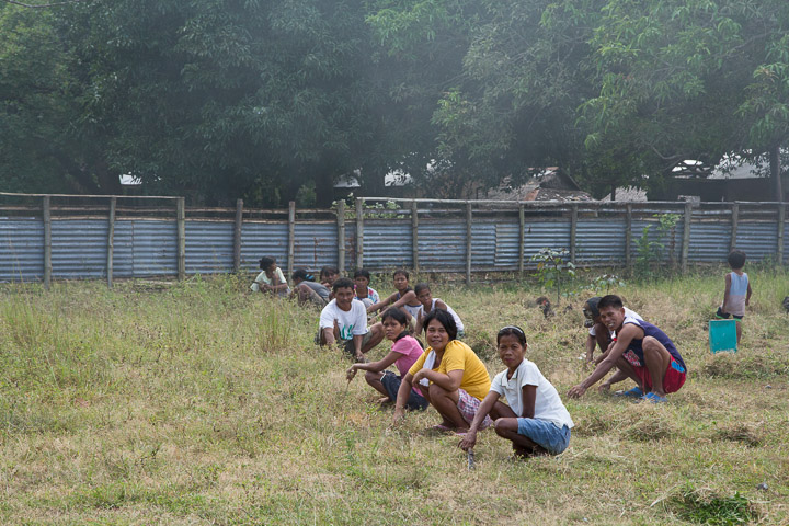 Parents d'élèves Tagbanua coupant l'herbe de la cour de l'école, Philippines © Camille Oger
